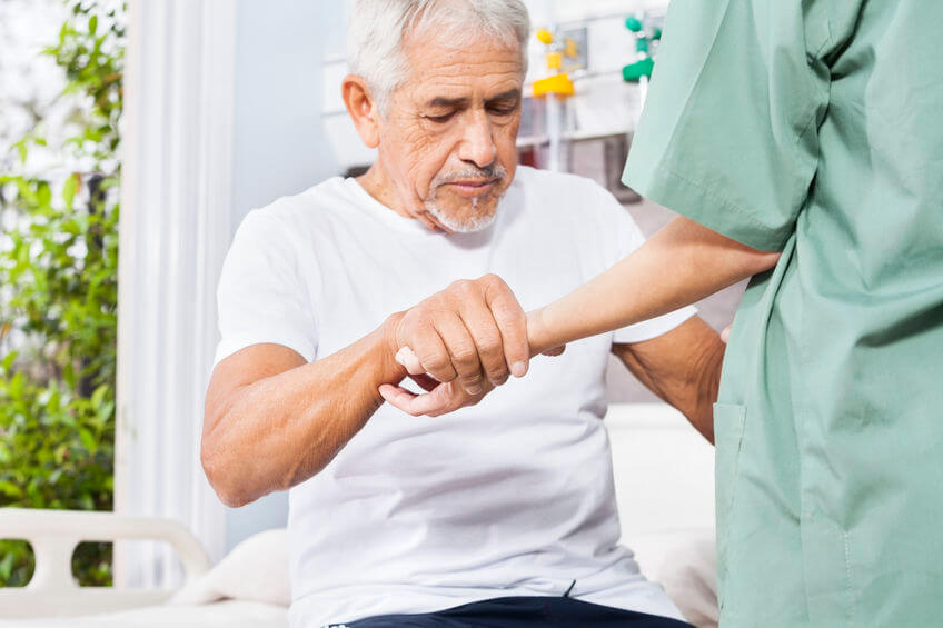 disabled senior patient holding hand of female nurse